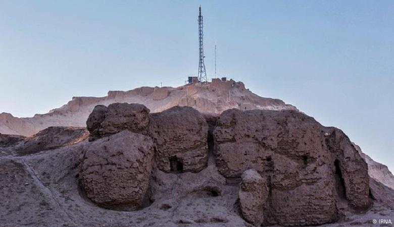 """Auf den historischen Lehmburgen """"Ardeshir"""" und """"Dokhtar"""" der Stadt Kerman, im Südosten des Iran, wurden Strommasten errichtet. Warum die zuständigen Behörden auf dem kulturellen Erbe aus vorislamischer Zeit diese Anlagen aufgestellt haben, ist unklar."""