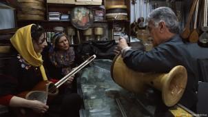 Szenenfoto: Die Sängerin Parvin Namazi singt in Begleitung von Sara Najafi und einem Instrumentenverkäufer
