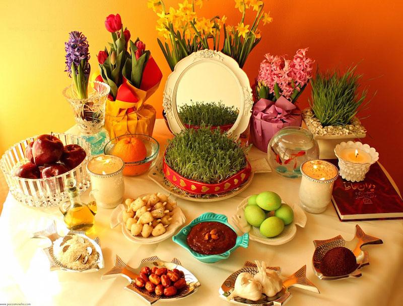 """Am 20. März, gegen 11:28 Uhr (MEZ) beginnt das neue iranische Jahr. Jede Region feiert das Neujahrsfest """"Nouruz"""" auf ihre Art und Weise. Zur Neujahrstradition der meisten IrannerInnen gehört eine große Tafel, genannt """"Sofreh-Haft-Sin"""", auf die sieben verschiedene Lebensmittel und Pflanzen gestellt werden, die in der persischen Sprache mit dem Buchstaben """"S"""" beginnen. Das sind in der Regel Sib (Apfel), Samanu (süßer Brei aus Weizenkeimen), Sir (Knoblauch), Sabzi (grüne Sprossen), Serkeh (Essig), Senjed (eine Art essbare Mehlbeere), Sekkeh (Geldmünze). Sie symbolisieren Fruchtbarkeit und Reichtum. """"Sofreh-Haft-Sin"""" bleibt dreizehn Tage lang stehen, denn so lange besuchen sich IranerInnen gegenseitig zum Nouruz."""