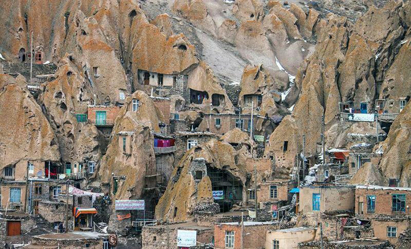 """Das Felsendorf """"Kandovan"""" in der iranischen Provinz Ost-Aserbaidschan zählt zum kulturellen Erbe des Iran. Über das Alter des Dorfes wird spekuliert – die Schätzungen variieren zwischen 700 und 6.000 Jahren. Die 120 Familien haben ihre Wohnungen in den Kegeln einer außergewöhnlichen Tuffsteinformation errichtet. Von außen sind nur die Treppenzugänge, sowie die farbigen Türen und Fenster zu sehen. Die einzelnen Terrassen des an einem steilen Berg angelegten Dorfes sind durch Holzbrücken miteinander verbunden. Auch das öffentliche Bad und die Moschee sind in die Felsen eingebaut worden. Die außergewöhnliche Verbindung von Landschaft und Architektur ist in den letzten Jahren zu einem Anziehungspunkt der heimischen und internationalen Touristen geworden. Die bislang bäuerliche Bevölkerung lebt von den regionalen Erzeugnissen, insbesondere aus der Schafzucht und dem Obstanbau."""