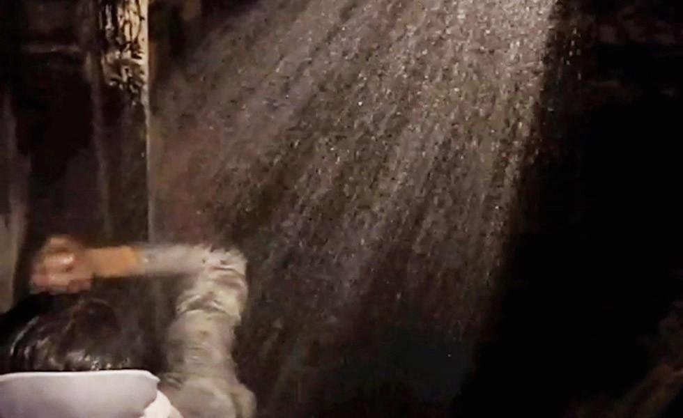 """""""Salam"""", Videostandbild (Video einer Performance), 7' 30"""", Aug. 2009, Yazd, Iran 2009 diente die Veranstaltung als Beispiel kulturellen Potenzials iranischer Kunst außerhalb der Hauptstadt. Es ist gängige Praxis in der Kunst, wie etwa im Falle der Avantgardisten, Performances zu nutzen, um ein unvertrautes Publikum unmittelbar anzusprechen. Die Beziehung zwischen Kunst und Leben ist außerhalb Teherans wenig vermittelt. Viele Kunstwerke, die abseits der Hauptstadt produziert werden, nehmen soziokulturelle Probleme auf und sprechen ihre Zielgruppe direkt an. Bei diesem Festival waren die Performances choreografiert: Sie waren miteinander verbunden und im ganzen Haus verteilt. Sie rissen das Publikum aus einer Aufführung zur nächsten mit. Pirouzmands Performance fand im Keller statt, wo eine Dusche in einem historischen Becken platziert war. Den Link zum Video finden Sie unten!"""