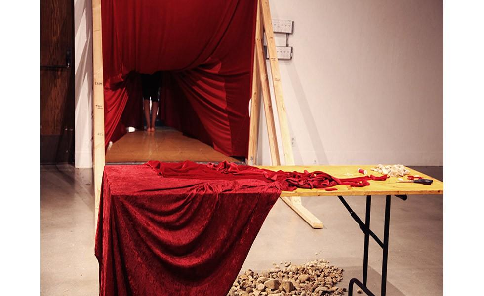 """""""Fühle den Samt"""", Videostandbild (Video einer Performance), 50"""", Okt. 2015, D300 Gallery, California Institute of the Arts, Valencia, USA """"Fühle den Samt"""" war eine zweistündige partizipatorische Performance. Nur jeweils eine Person konnte die Galerie betreten, und das nur unter der Bedingung, dass sie ein 23 Kilogramm schweres Kleidungsstück trug, das aus runden Steinen umhüllt mit rotem Samt gefertigt war. Den Link zum Video finden Sie unten!"""
