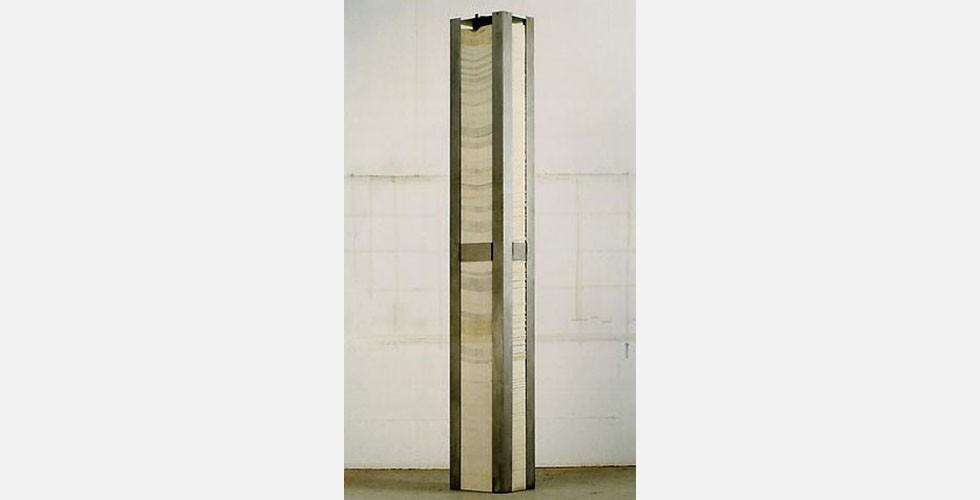 """""""Eine Zahl zwischen Null und Eins"""", Stahl und Papier, 264,2 x 38,1 x 27,9cm, 1970 Später interessierte sich Armajani für die Konzeptkunstbewegung und gab die Verwendung von iranischen Motiven auf. Viele Arbeiten der zweiten Phase seines Werks stellen nutzlose wissenschaftliche Erfindungen dar. Diese Arbeiten wurden von der amerikanischen Kunstszene überaus positiv aufgenommen und machten den Künstler berühmt. Das Werk oben stellt ein Beispiel dafür dar. Es ist eine Dezimalzahl auf 25.974 Seiten Papier ausgedruckt. Die Zahl besteht aus einer Reihe von 205.714.080 Nullen und einer Eins. Das Interesse des Künstlers an unpraktischen wissenschaftlichen Konfigurationen entstammt seiner akademischen Ausbildung im Bereich Philosophie und Mathematik in den USA."""
