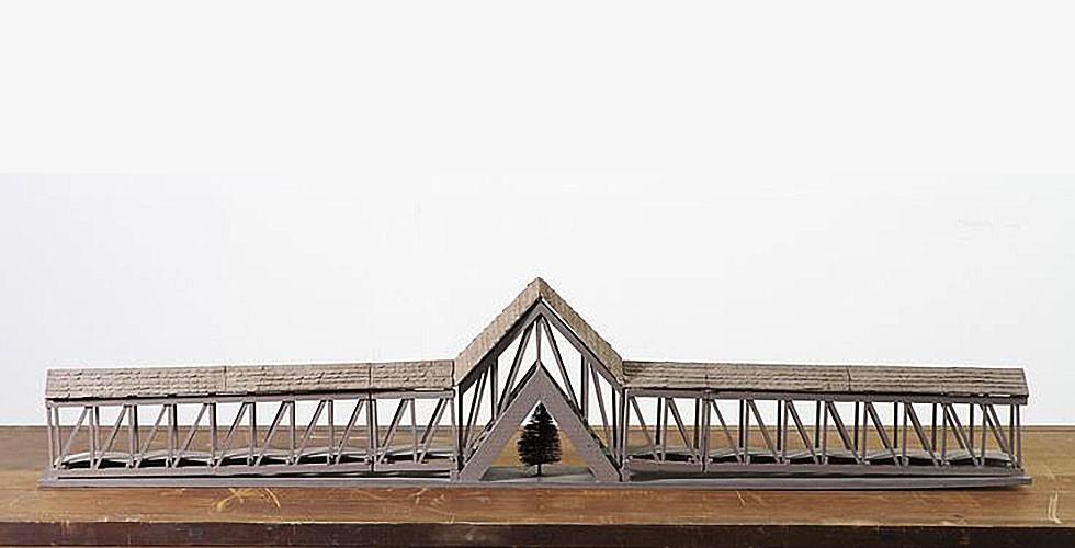"""""""Brücke über einem Baum"""", Balsaholz, 27,5 x 127,5 x 11cm, Sammlung Max Protetch, New York, 1970 Seine nächste künstlerische Etappe zeichnet sich aus durch die Besessenheit von Architektur als künstlerischer Ausdrucksform. Armajanis früheres Interesse an den Darstellungen von Raum in persischen Miniaturen führte ihn zum Aufbau seiner bezaubernden Räume, in denen konstruktivistische Ästhetik mit amerikanischer Architektur der Moderne verknüpft ist. Durch diese Arbeiten wurde Armajani zum einflussreichen Akteur im Bereich """"Public Art"""" in den USA. Er begann, Leseräume und Gartenlauben aufzubauen, die der Dichtung und der Philosophie gewidmet waren. Eine Sucht nach Text, die schon in seiner ersten künstlerischen Etappe vorhanden war, tritt erneut in seiner Arbeit auf. Dies äußert sich nicht nur in der Funktion der Bauwerke, sondern auch in den Zitaten, die auf jenen eingetragen sind. Armajani sieht seine Werke als inspiriert vom Vorhandensein des Schreibens in der iranischen Architektur, wo Verse aus dem Koran oder persische Dichtungen die öffentlichen Gebäude verzieren."""