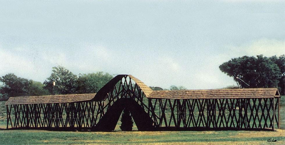 """""""Brücke über einem Baum"""", Holz, Fichte, 335 x 2591 x 122cm, Minneapolis, 1970 Zu den bekanntesten Werken Armajanis gehören seine Brücken. Für ihn ist die Brücke ein philosophisches Konstrukt. Nicht nur verbindet sie verschiedene Gebiete, sondern sie schafft auch einen Zwischenraum, in dem der Beobachter sowie das, was vor und was hinter ihm liegt, zusammenkommen."""