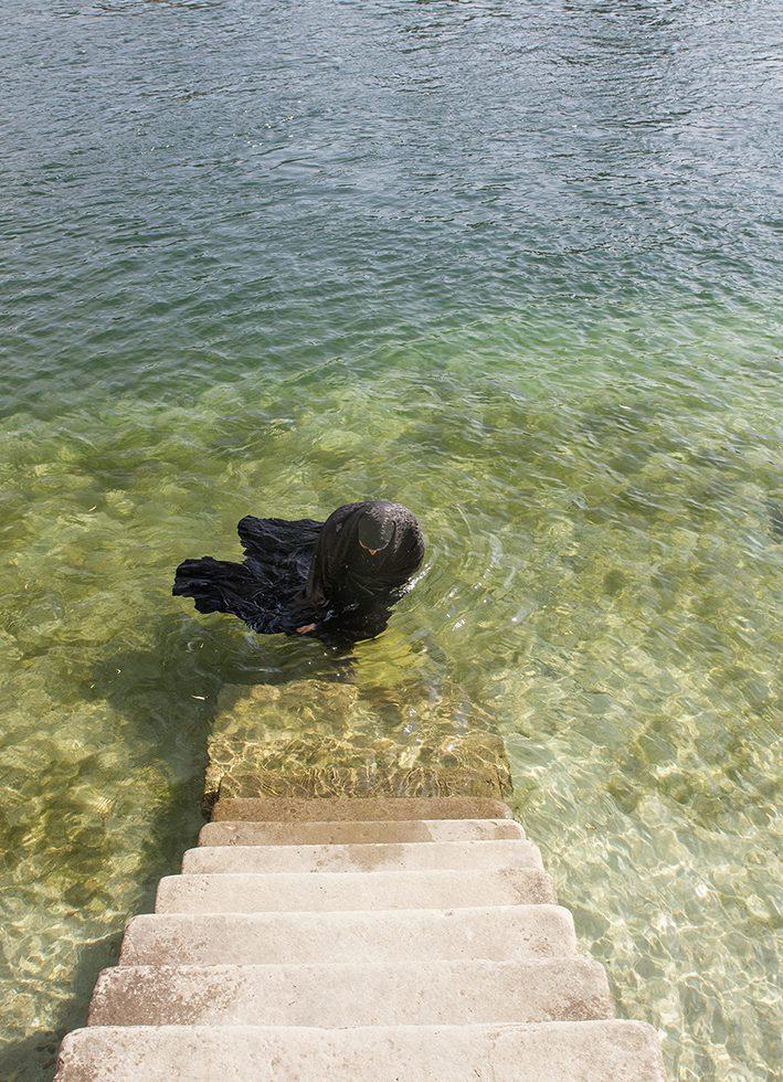 Parastou Forouhar erkundete Stein am Rhein, die Umgebung, die Landschaft und die jeweilige Atmosphäre, nahm diese liebliche Schönheit in sich auf und erschloss sich unterschiedliche Orte für ihre inszenierten Fotografien: Eine schwarz verhüllte Gestalt bewegt sich durch die Gassen, wandelt in der Natur, steigt aus dem klaren Wasser des Rheins. Sie tanzt und bewegt sich an verschiedenen Plätzen im Innen- und Außenraum und tritt auf diese Weise in Kontakt mit ihm.