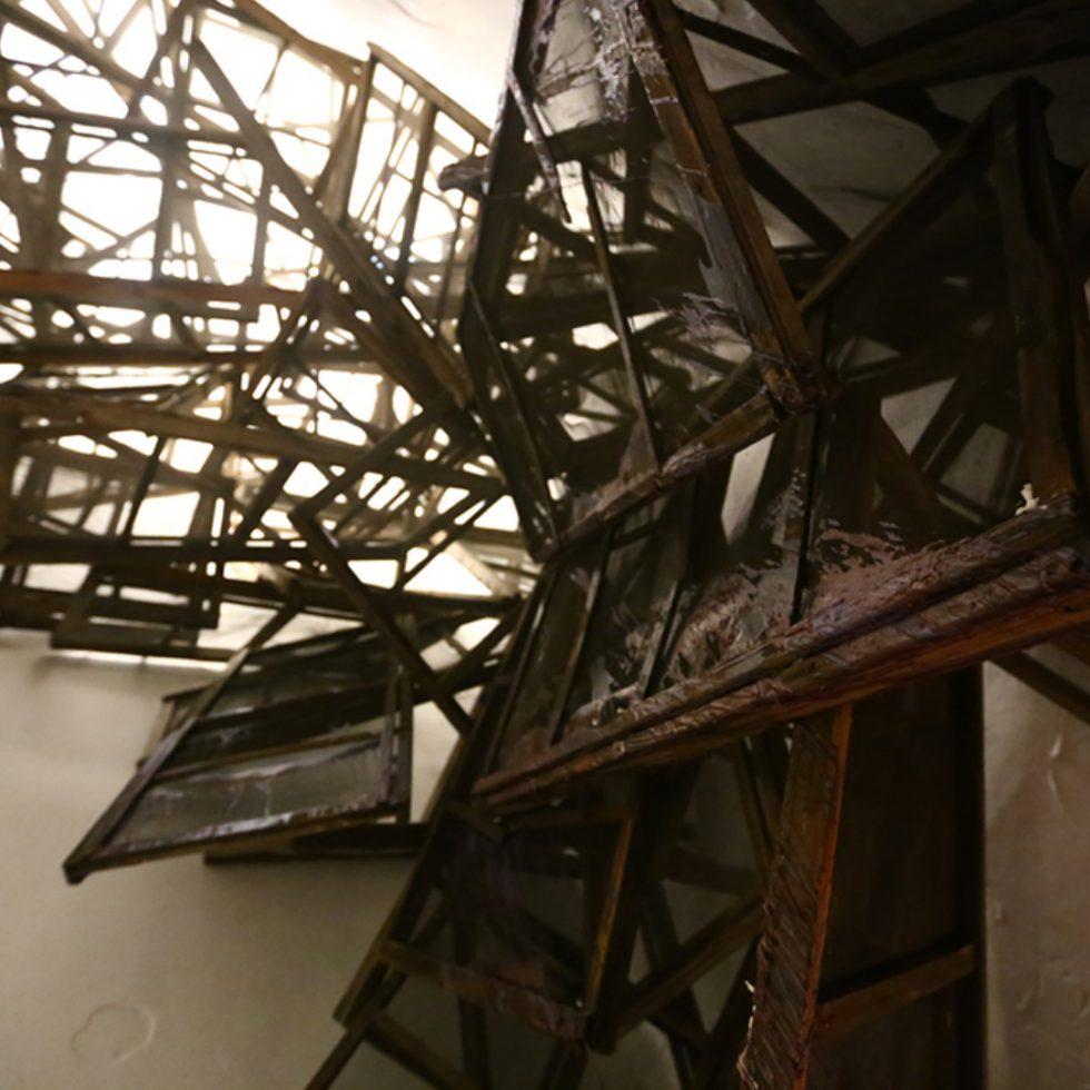 Mahroumis neuste Arbeit, die Mitte dieses Jahres in der Mohsen Gallery zu sehen war, ist 'A Disappointing Idea to Build a Roof on a Lit Candle' (2018). Sie zielt ähnlich wie AH(sigh) auf den Kontext des Metaphorischen. Dort ist es die Härte des Betons, die uns die Schwierigkeit und Problematik des Erinnerns aufweist. Hier ist es eine groß angelegte, komplexe Installation, die im Zusammenspiel mit dem Titel auf das zielt, was uns präsent ist, was unsere Erfahrung der Gegenwart ausmacht. Gleichzeitig zielt diese Arbeit auf den Zweifel und das Infragestellen ihrer eigenen Existenz. Im Ganzen lässt Mahroumi zwei gegensätzliche und sich widersprechende Konstruktionen gegeneinander laufen, um dann auf einer weiteren, dritten Ebene eben diese Konfrontation als solche, auch die Konstruktion von Bildern, Metaphern selbst, in den Raum zu stellen. Da ist die brennende Kerze, die sich durch eine Dia-Projektion von achtzig Aufnahmen vergegenwärtigt, begleitet durch das maschinelle Geräusch der Aneinanderreihung der einzelnen Kerzenbilder.