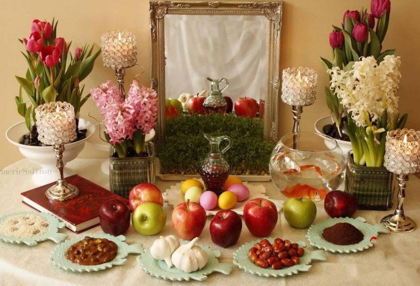 """Am 20. März, gegen 23:30 Uhr (MEZ) beginnt das neue iranische Jahr. Jede Region feiert das Neujahrsfest """"Nouruz"""" auf ihre Art und Weise. Zur Neujahrstradition der meisten Iranner*innen gehört eine große Tafel, genannt """"Sofreh-Haft-Sin"""", auf die sieben verschiedene Lebensmittel und Pflanzen gestellt werden, die in der persischen Sprache mit dem Buchstaben """"S"""" beginnen. Das sind in der Regel Sib (Apfel), Samanu (süßer Brei aus Weizenkeimen), Sir (Knoblauch), Sabzi (grüne Sprossen), Serkeh (Essig), Senjed (eine Art essbare Mehlbeere), Sekkeh (Geldmünze). Sie symbolisieren Fruchtbarkeit und Reichtum. """"Sofreh-Haft-Sin"""" bleibt dreizehn Tage lang stehen, denn so lange besuchen sich Iraner*innen gegenseitig zum Nouruz."""