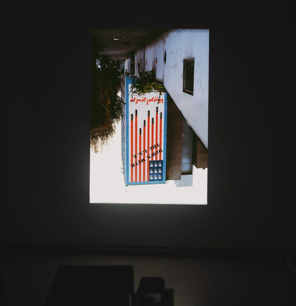 Up and Down with the USA - Slide Projection, dimensions variable, 2012 Die Diaprojektion 'Up and Down with the USA' (2012) referiert auf ein kurz nach der Revolution entstandenes Mural im Zentrum Teherans. Das von Razmi abfotografierte Bild dieses Wandgemäldes dreht sie kurzerhand um, die fallenden Bomben schießen nach oben. Auch hier eine Umkehrung, eine Umkehrung, die simpel erscheint und die Welt auf den Kopf stellt, aber eine, die hinter jedem Blick stattfindet, der auf das Original fällt. Das Mural selbst ist der Klassiker schlechthin, ihn zu übermalen wäre ein politisch motiviertes Unternehmen. Selbst in der ideologischen Affirmation ist der historische Kontext dieses monumentalen Großgemäldes eingeschrieben, dass seine Aussagekraft auf eine geschichtliche Erinnerung reduziert wird. Das Spiel selbst, das Spiel mit dem Zeichen, aktualisiert den Inhalt, verdreht ihn zu gedanklichen Erwägungen über Vergangenheit und Gegenwart, aber auch dazu, eben nicht auf den Gedanken zu kommen, dass es nur eine Geschichte gebe.