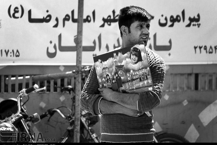 In der Stadt Mashhad, im Nordosten des Iran, besuchen jährlich mehrere Millionen Schiiten aus der ganzen Welt den Schrein des achten schiitischen Imam Reza. Da es verboten ist den Schreien zu fotografieren, lassen sich die PilgerInnen in den Fotostudios vor einem Bild des Schreins abbilden. Da es immer mehr Fotostudios in der Umgebung des Schreins gibt, gewinnt die Werbung um Kunden immer mehr an Bedeutung. So beschäftigen viele Studios junge Männer in den Straßen, die die Werbetrommel für sie rühren. Für diesen Job bedarf man einer lauten Stimme gepaart mit Charme und einem ansprechenden Aussehen.