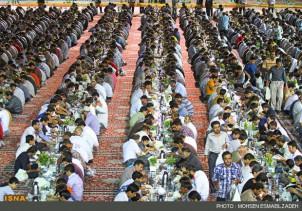 """Laut Angaben der Stiftung """"Astan Ghods Razavi"""" (AGR) nehmen täglich bis zu 12.000 Menschen am allabendlichen Fastenbrechen im Hof des Schreines vom Imam Reza teil. Imam Reza ist einer der wichtigsten Heiligen der Schiiten. Diese traditionelle mildtätige Verköstigung wird durch die finanzkräftige AGR bereitgestellt, die den Schrein verwaltet. Für die Vorbereitungen der täglichen Zusammenkunft sind nach Angaben der AGR ca. 3000 Freiwillige im Einsatz. Etwa 500 KöchInnen und Küchenhilfen richten in der gigantischen Küche des Schreins täglich 2.400 kg Reis und mehr als 900 kg Fleisch an. Während des Fastenmonats Ramadan ist es den gläubigen Muslimen in der Zeit zwischen Sonnenaufgang und Sonnenuntergang nicht gestattet zu essen oder zu trinken. Ältere Menschen, Kranke oder schwangere Frauen sind von dieser religiösen Pflicht befreit. Der Fastenmonat Ramadan hat am 9. Juli begonnen und endet mit einem großen Fest am 8. August."""