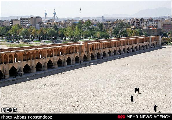 """Der Fluss Zayandeh-Rud, der durch die iranische Stadt Isfahan fließt, ist diesen Sommer erneut ausgetrocknet. Dies geschieht nun zum sechsten Mal in Folge. Nach Angaben der Behörden ist der Wasserspiegel in der gesamten Region um Isfahan aufgrund von sinkender Niederschlagsmenge stark zurückgegangen. Zayandeh-Rud war einst der wasserreichste Fluss im Zentraliran und einer der wenigen, der ganzjährig Wasser führten. Auf dem Foto ist auch die Brücke """"Sio-seh-pol"""" zu sehen. Sie ist eine der drei wichtigen Brücken über den Zayandeh Rud. Das 290,4 Meter lange und 13,5 Meter historische Bauwerk wurde in der Safawiden-Zeit um 1630 erbaut."""
