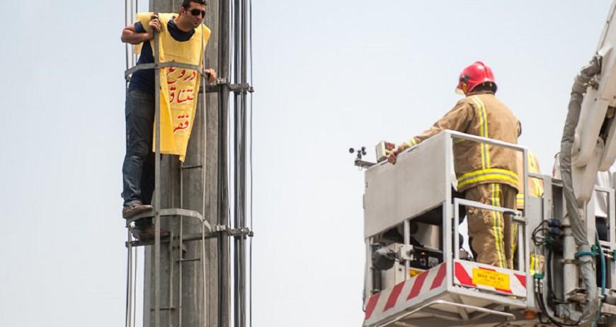 """Am 8. Juli rückten die Teheraner Feuerwehrmänner mit Bodenmatten zum """"Siebte Tir Platz"""" vor, um einen Mann vor dem Selbstmord zu retten. Der 36jährige wollte sich von einem Mast in die Tiefe stürzen. Den Rettungskräften gelang es, den lebensmüden Mann durch Gespräche von seinem Vorhaben abzubringen. Er trug ein gelbes Transparent um den Hals, auf dem Stand: """"Lüge, Armut, Ersticken""""."""