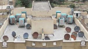 Satellitenschüsseln und Klimaanlagen auf dem Dach eines Teheraner Wohnhauses!